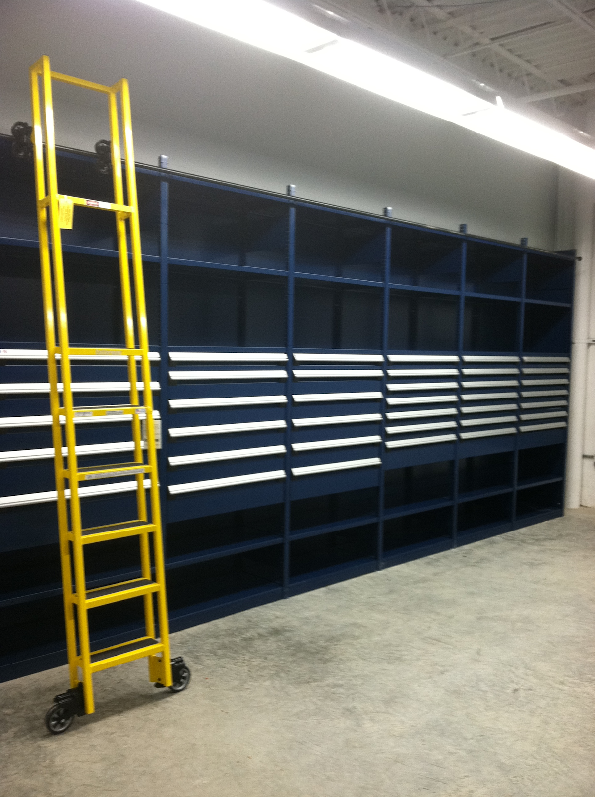 High-rise warehouse shelving with drawers and mobile ladder